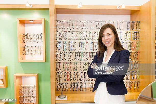 woman in front of eye glasses display cabinet arms crossed looking at camera smiling - sigrid gombert stock-fotos und bilder
