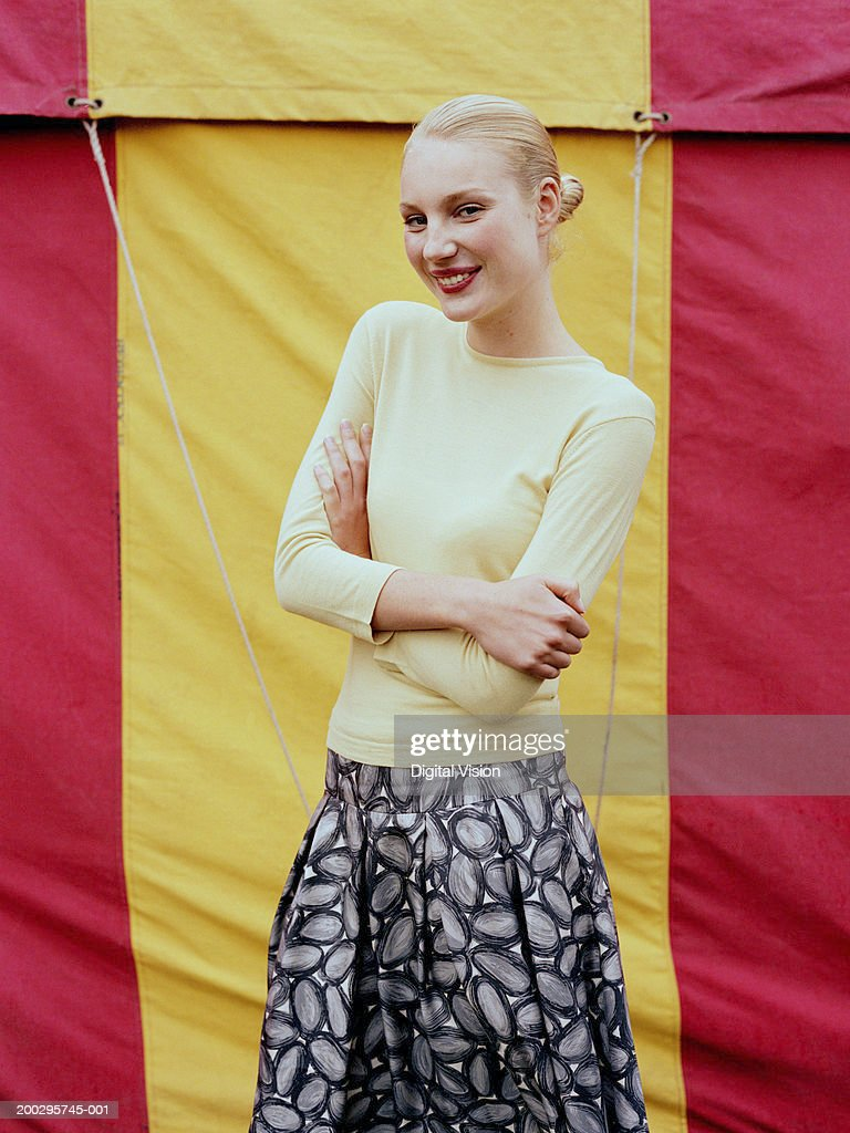 Woman in front of fairground tent, arms folded, smiling, portrait : Stock Photo