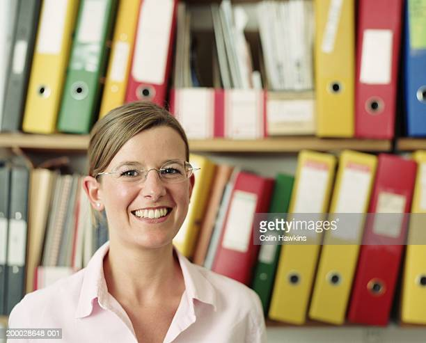 woman in front of files, smiling, portrait (focus on face) - blouse ストックフォトと画像