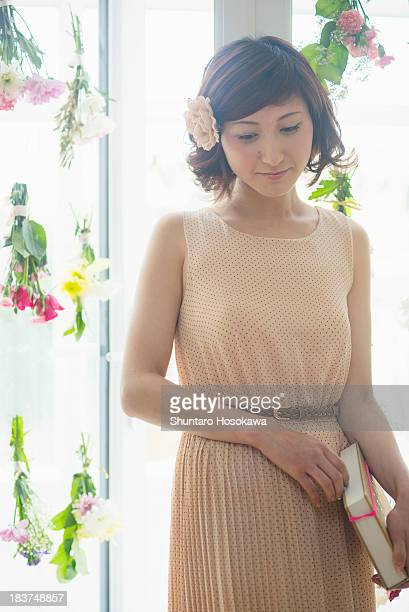 Woman in front of glass door with dangling flowers