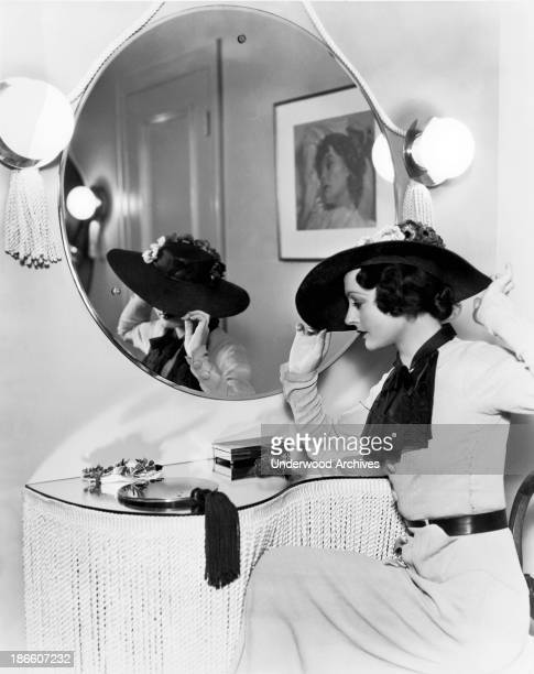 A woman in front of her mirror makes final adjustments to her hat Hollywood California late 1940s