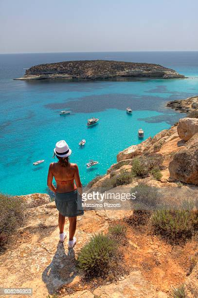 Woman in front of Island of Rabbits at Lampedusa