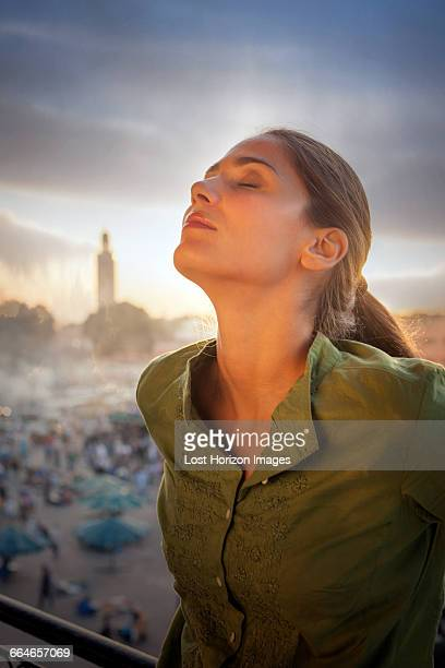 woman in front of jemaa el-fnaa square, head back, eyes closed, marrakesh, morocco - femme marocaine photos et images de collection