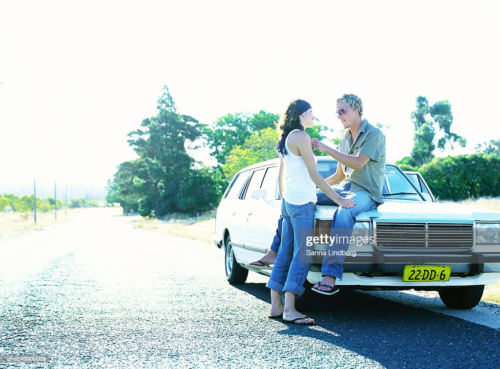 Woman in front of man sitting on car hood : Stockfoto
