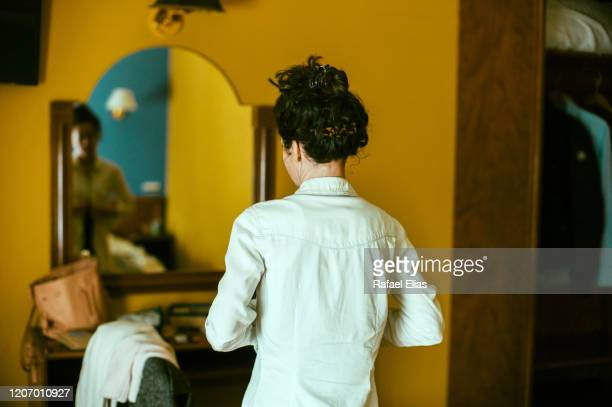 woman in front of mirror changing her blouse - ひげそり用鏡 ストックフォトと画像