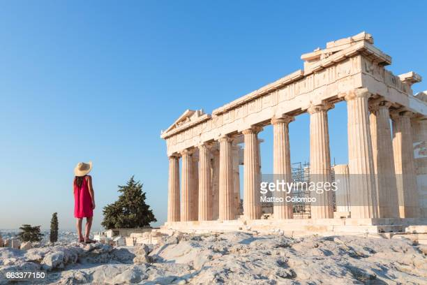 woman in front of parthenon temple on the acropolis, athens, greece - oude ruïne stockfoto's en -beelden