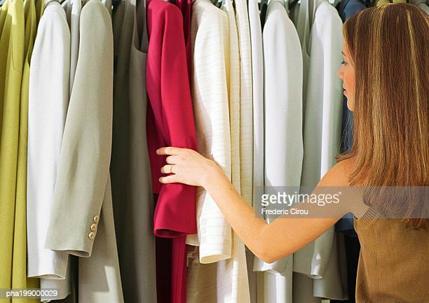 Woman in front of rack of suits, rear view