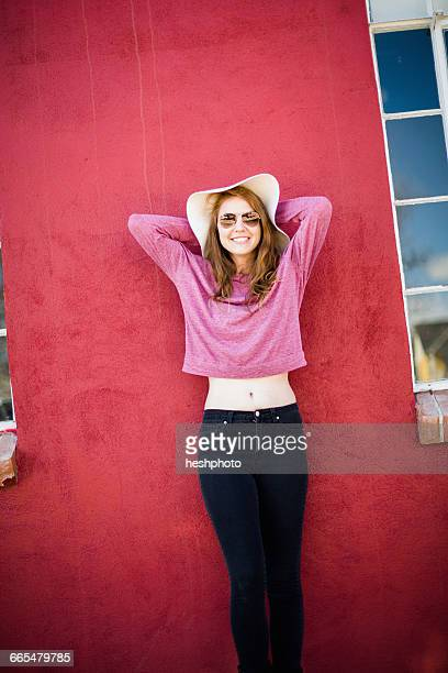 woman in front of red wall wearing sunhat and sunglasses smiling - heshphoto stockfoto's en -beelden