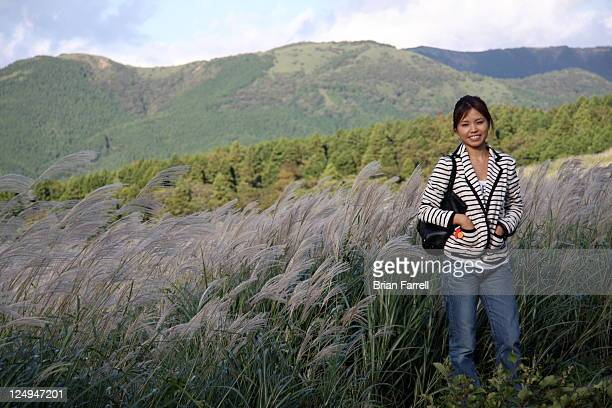 Woman in front of susuki grass and mountains