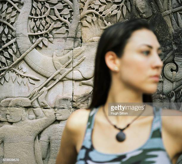 woman in front of temple carvings - hugh sitton stock pictures, royalty-free photos & images