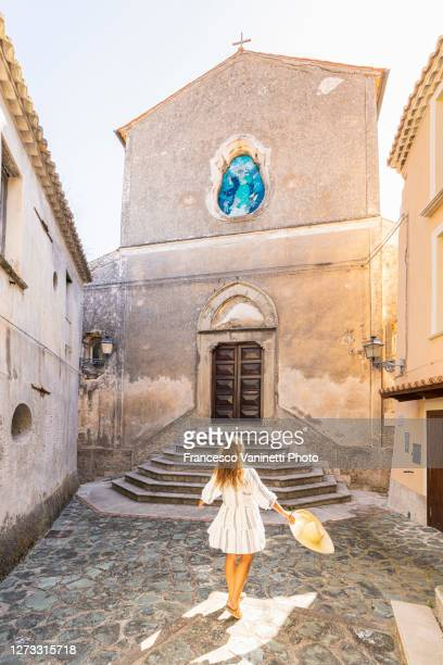 woman in front of the church of santa maria assunta, belmonte calabro, italy. - calabria stock pictures, royalty-free photos & images