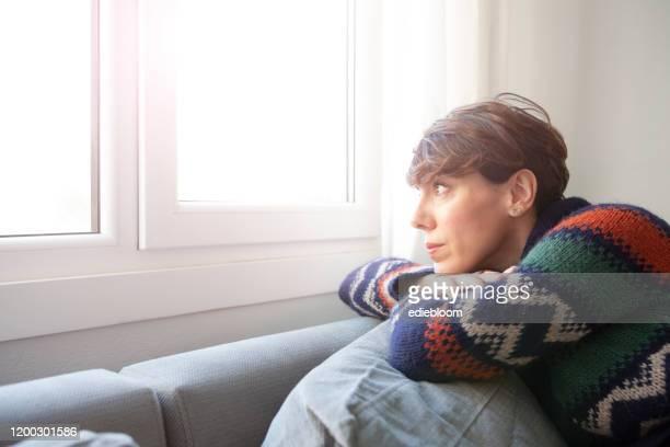 vrouw voor het raam - eenzaamheid stockfoto's en -beelden