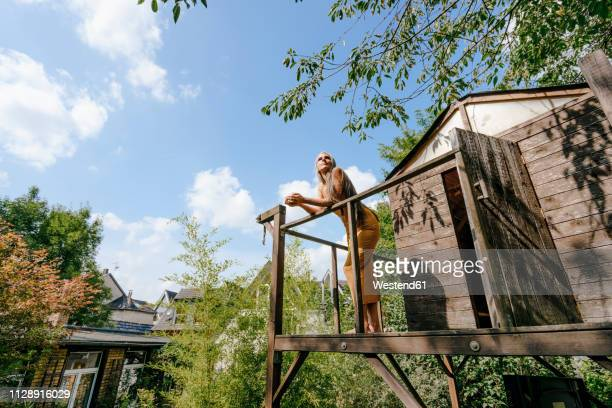woman in front of tree house enjoying sunlight - tree house stock pictures, royalty-free photos & images
