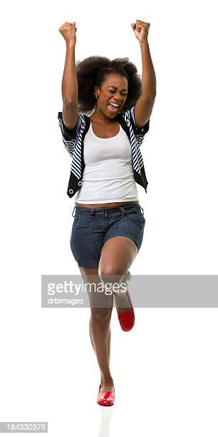 Woman in front of white background with her arms in the air