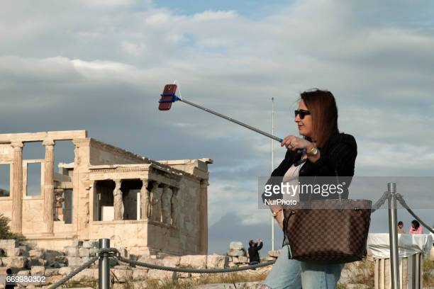 A woman in front the ancient temple of Erechtheion uses a selfie stick to take a snap shot at the Acropolis Hill in Athens Greece on April 18 2017...