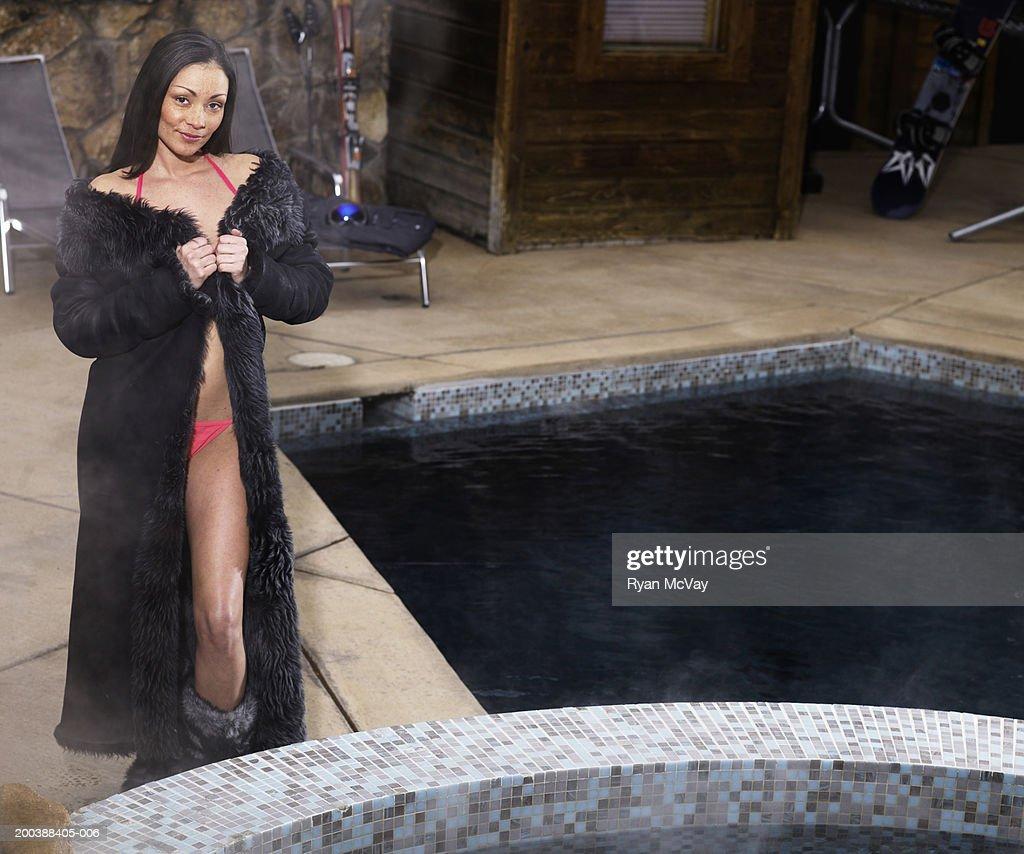 Woman in fur coat and bikini standing beside swimming pool for Folie fur pool