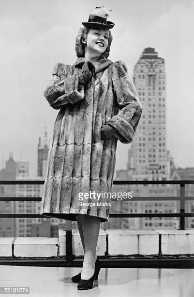 Woman in fur coat and fancy hat standing on outside terrace (B&W)