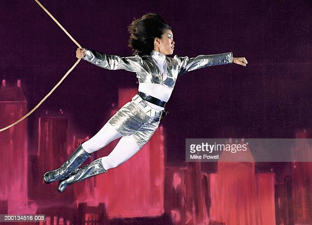 Woman in futuristic costume hanging from rope