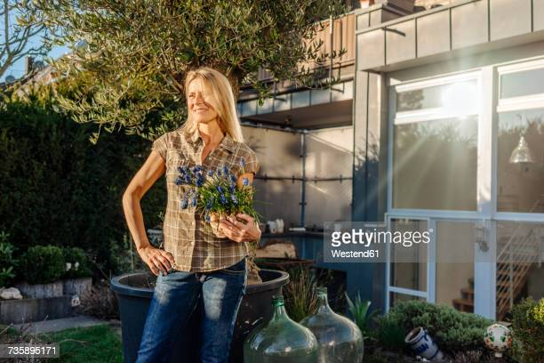 woman in garden holding grape hyacinths - grape hyacinth stock pictures, royalty-free photos & images