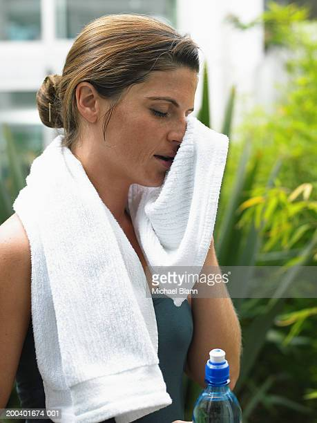 Woman in garden holding water bottle, wiping face with towel