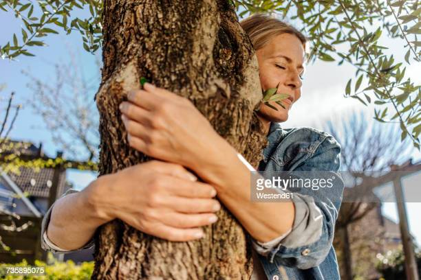 Woman in garden hugging a tree