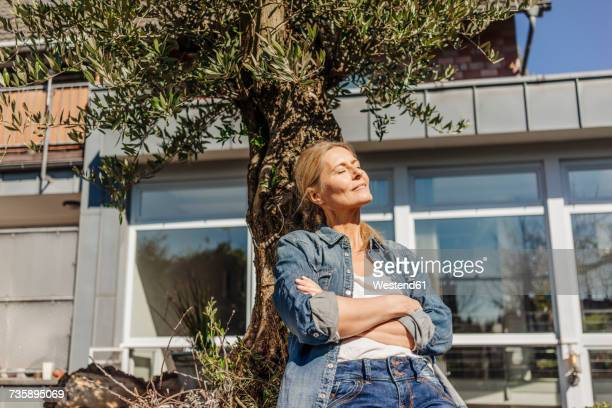 Woman in garden leaning against a tree