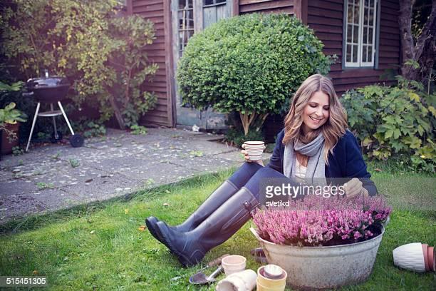 woman in garden. - rubberlaars stockfoto's en -beelden