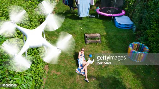 Woman in garden sunbathing, being filmed by drone