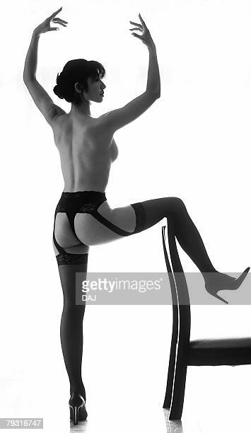 Woman in garter belt and stockings, posing and putting a leg on a chair, black and white, rear view, white background