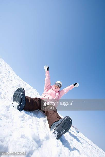 Woman in goggles cheering in snow
