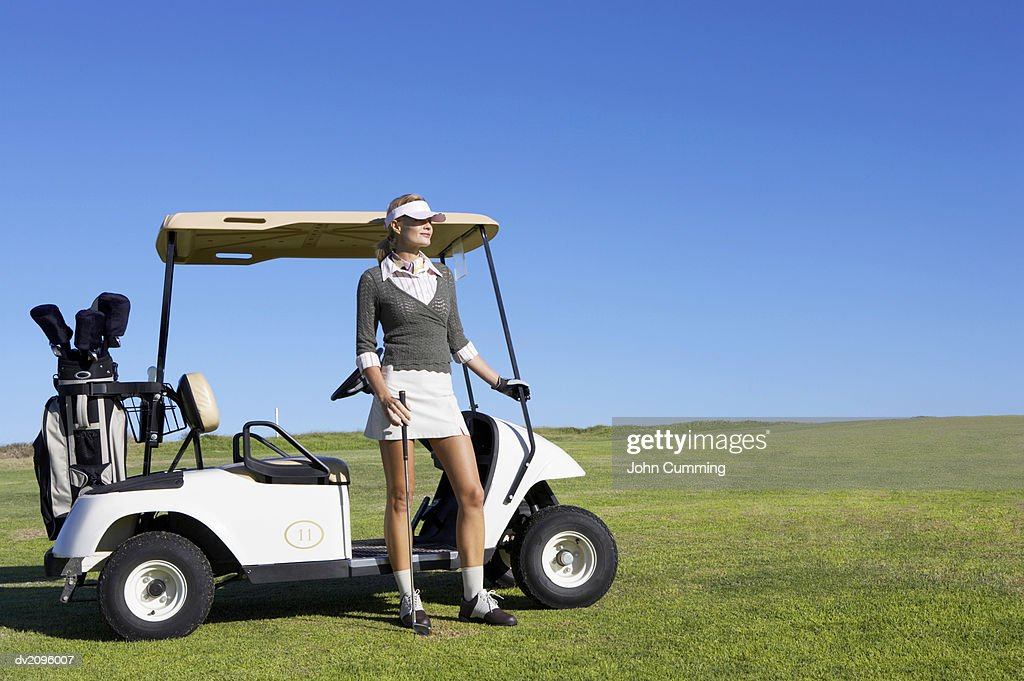 Woman in Golf wear Standing Next to a Golf Buggy : Stock Photo