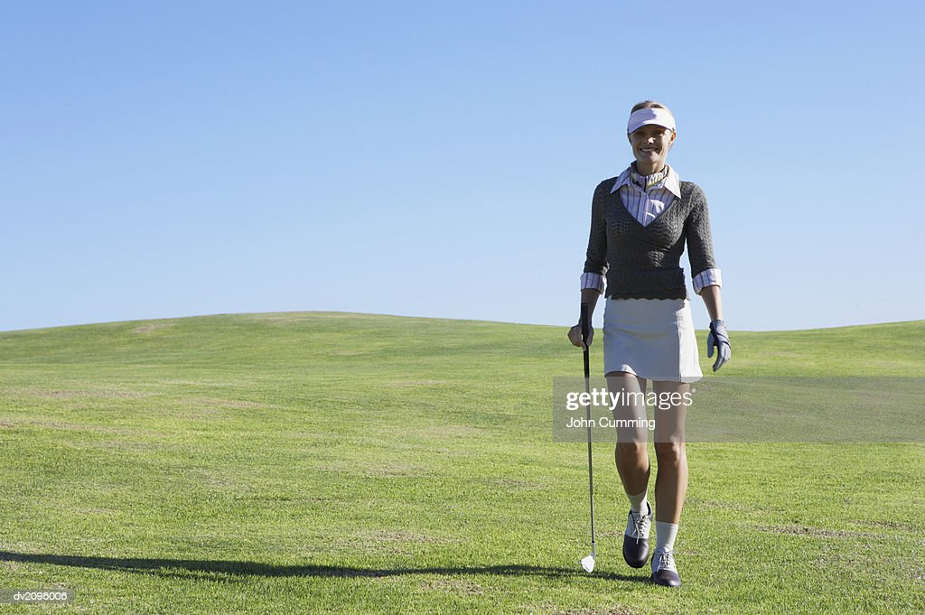 Woman in Golf wear Walking on a Putting Green : Stock Photo