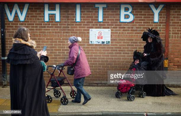 A woman in goth clothing poses with a doll in a pushchair in front of a 'Whitby' sign during Whitby goth Weekend on October 27 2018 in Whitby England...