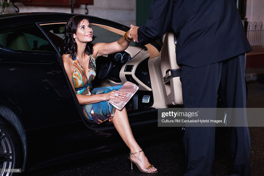 Woman in gown climbing out of car : Stock Photo