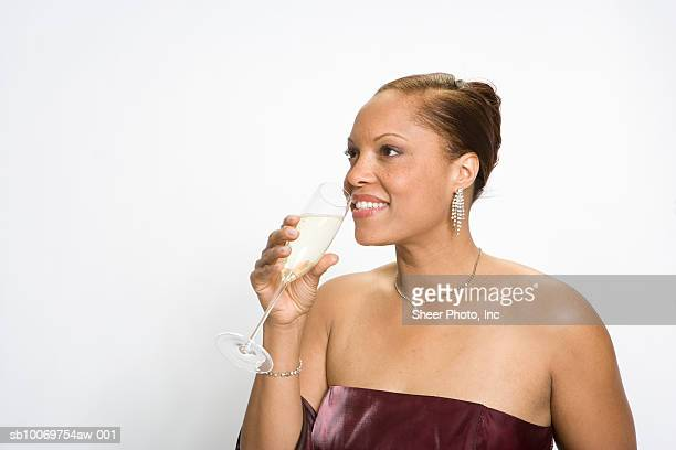 Woman in gown drinking champagne on white background