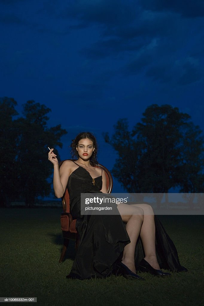 Woman in gown smoking cigarette on velvet chair in park at night : Foto stock
