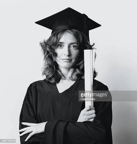 woman in graduation cap and gown, arms folded - headhunters stock pictures, royalty-free photos & images