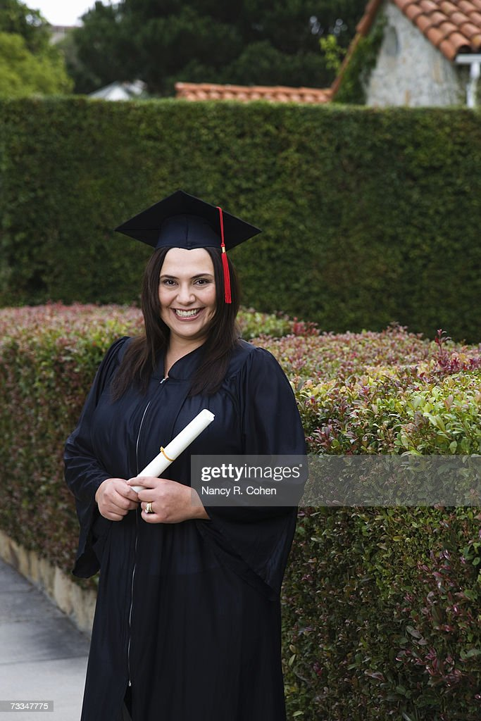 Woman In Graduation Gown And Mortarboard Smiling Portrait Stock ...