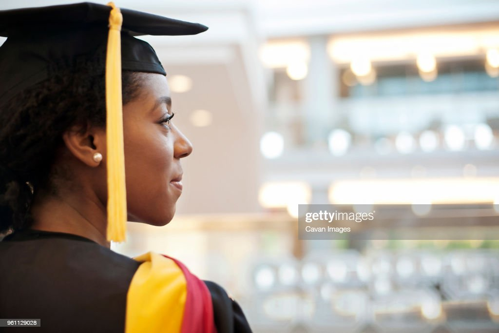 Woman in graduation gown looking away : Stock Photo