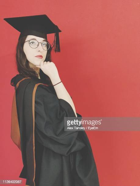 woman in graduation gown posing by red background - ラニーメイド ストックフォトと画像