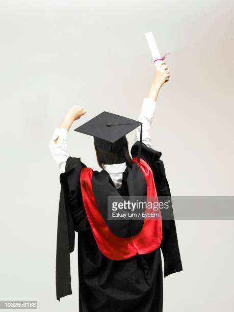 woman in graduation gown standing against white background - graduation background stock pictures, royalty-free photos & images