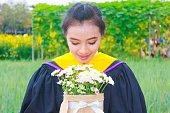 woman graduation gown with flowers at