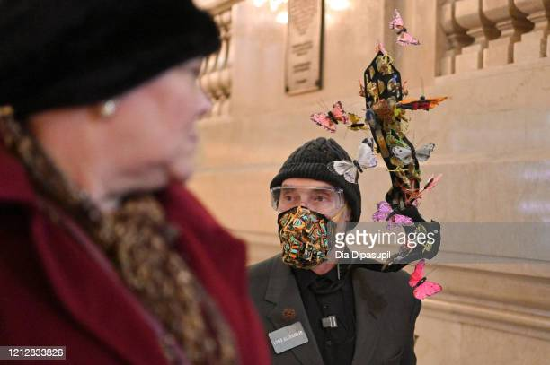Woman in Grand Central Terminal looks at visual artist Lynx Alexander wearing artwork he created representing COVID-19 as the coronavirus continues...