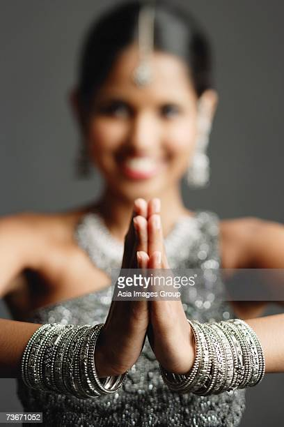 woman in gray sari smiling at camera, hands together, selective focus - prayer pose greeting bildbanksfoton och bilder