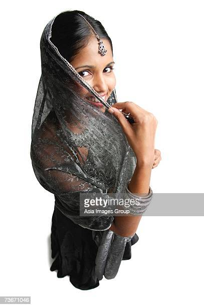 Woman in gray sari standing against white background, shielding face scarf