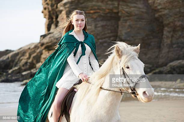 Woman in green cloak riding horse on beach