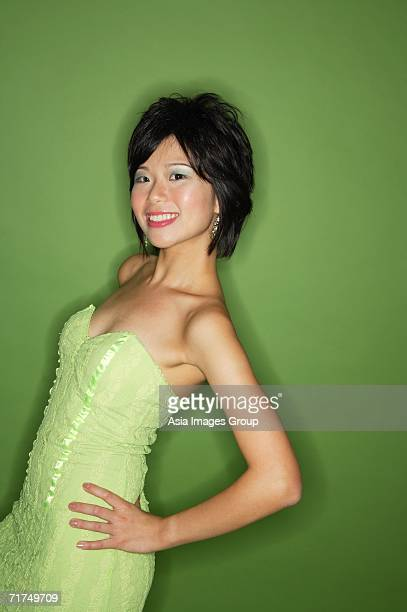 Woman in green dress, hands on hip, smiling at camera
