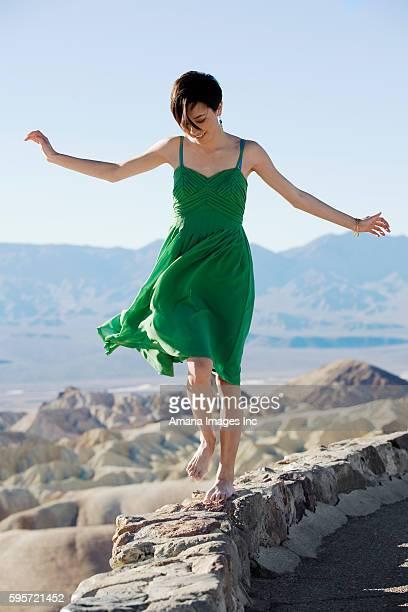 Woman in Green Dress Walking on Stone Wall