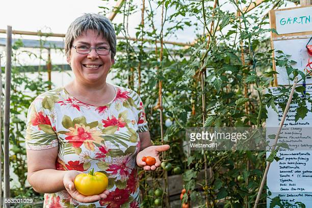 Woman in greenhouse holding red and yellow tomato