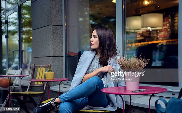 a woman in grey coat and blue jeans is waiting for someone at the cafe - written date stock pictures, royalty-free photos & images